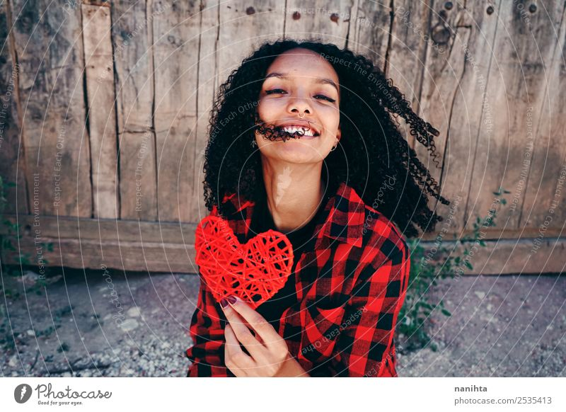 Happy young woman holding a red heart Lifestyle Style Design Joy Hair and hairstyles Healthy Wellness Harmonious Human being Feminine Young woman