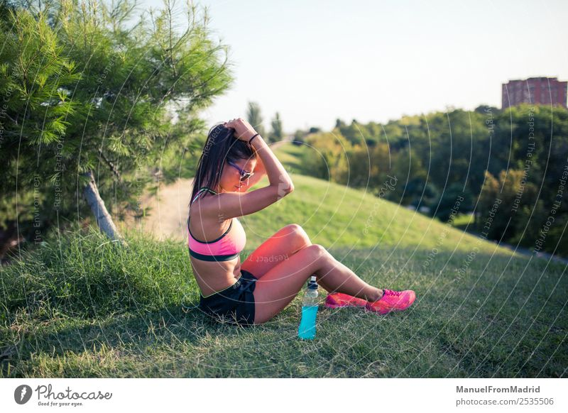 athletic woman resting Bottle Lifestyle Beautiful Summer Sports Woman Adults Nature Park Fitness Sit Energy workout Runner training Resting isotonic drink young