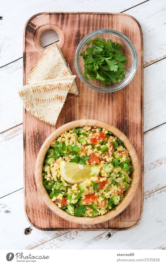 Tabbouleh salad with couscous on white wood. Top view. Table Salad Vegetable Tomato Cucumber Parsley Mint Vegan diet Vegetarian diet Healthy Healthy Eating