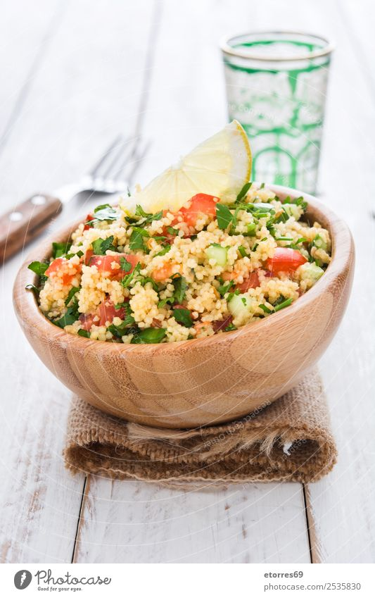 Tabbouleh salad with couscous on white wood. Table Salad Vegetable Tomato Cucumber Parsley Mint Vegan diet Vegetarian diet Healthy Healthy Eating Nutrition Diet