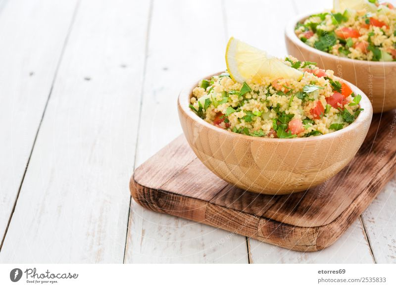 Tabbouleh salad with couscous on white wooden table Table Salad Vegetable Tomato Cucumber Parsley Mint Vegan diet Vegetarian diet Healthy Healthy Eating