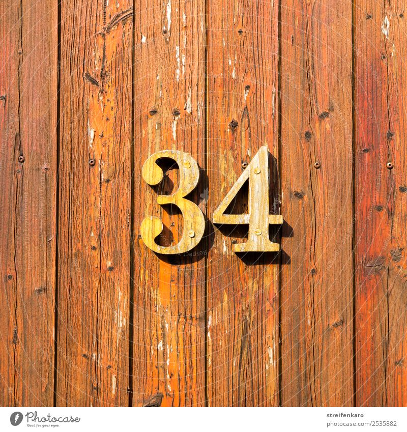 Wooden numbers 34 on one of the wooden slatted doors Flat (apartment) House (Residential Structure) House number Building Door Digits and numbers Sign Esthetic
