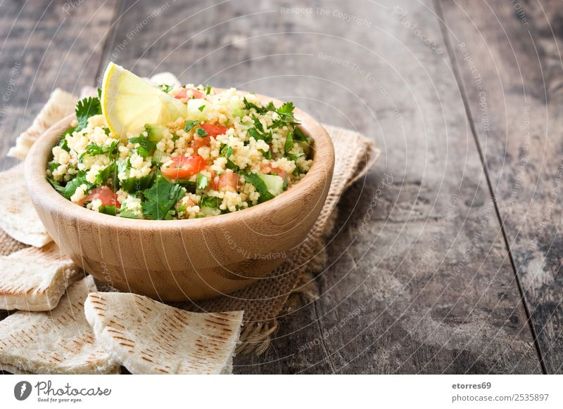 Tabbouleh salad on wooden table Table Salad couscous Vegetable Tomato Cucumber Parsley Mint Vegan diet Vegetarian diet Healthy Eating Nutrition Diet Bowl Lemon