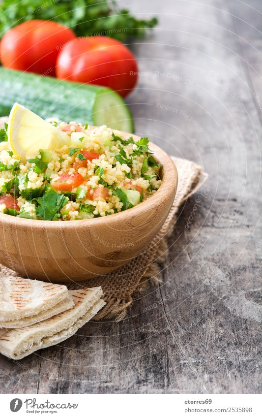 Tabbouleh salad and ingredients on wood Table Salad couscous Vegetable Tomato Cucumber Parsley Mint Vegan diet Vegetarian diet Healthy Eating Nutrition Diet