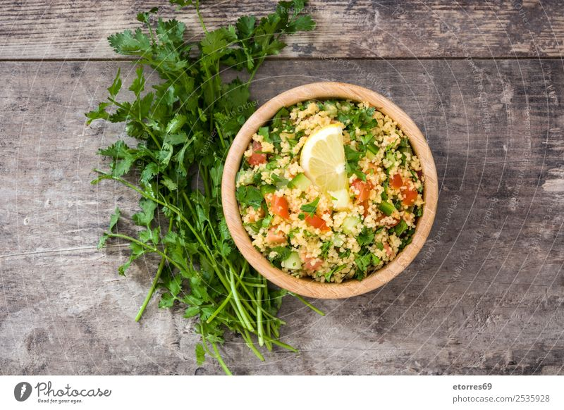 Tabbouleh salad with couscous on a wood. Table Salad Vegetable Tomato Cucumber Parsley Mint Vegan diet Vegetarian diet Healthy Healthy Eating Nutrition Diet