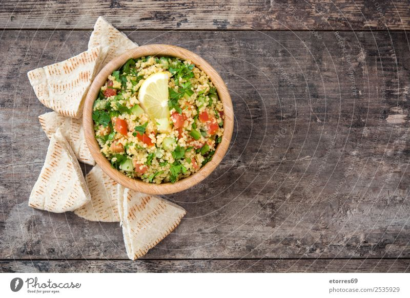 Tabbouleh salad with couscous on a wood Table Salad Vegetable Tomato Cucumber Parsley Mint Vegan diet Vegetarian diet Healthy Healthy Eating Nutrition Diet Bowl
