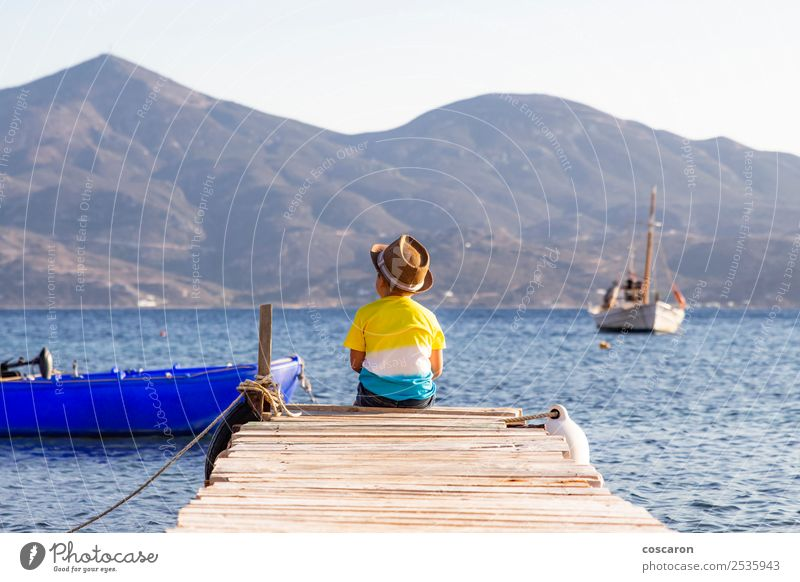 Little boy on a dock sitting on his back looking to the ocean Child Human being Sky Nature Vacation & Travel Summer Blue White Ocean Loneliness Joy Beach