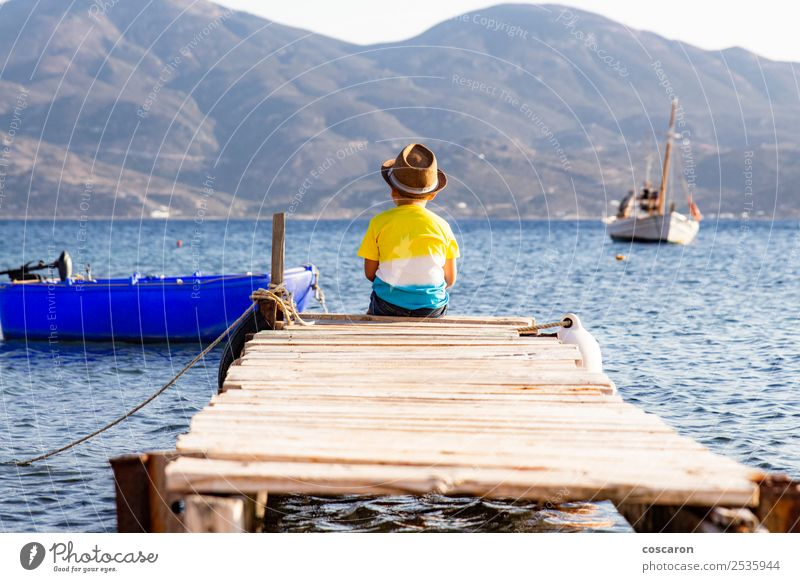Little boy on a dock sitting on his back looking to the ocean Lifestyle Joy Happy Leisure and hobbies Vacation & Travel Summer Beach Ocean Child Human being