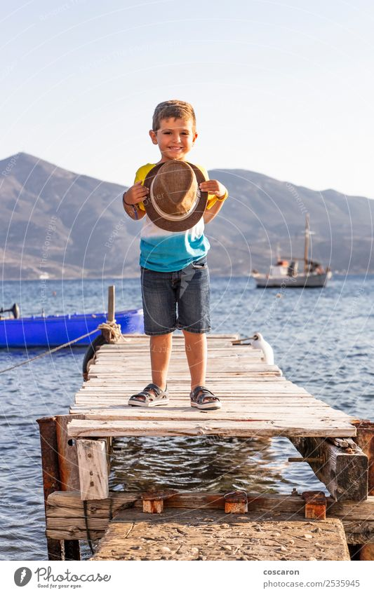 Portrait of a little kid on a dock with a hat in his hands Child Human being Sky Nature Vacation & Travel Man Summer Blue Beautiful White Ocean Relaxation Beach