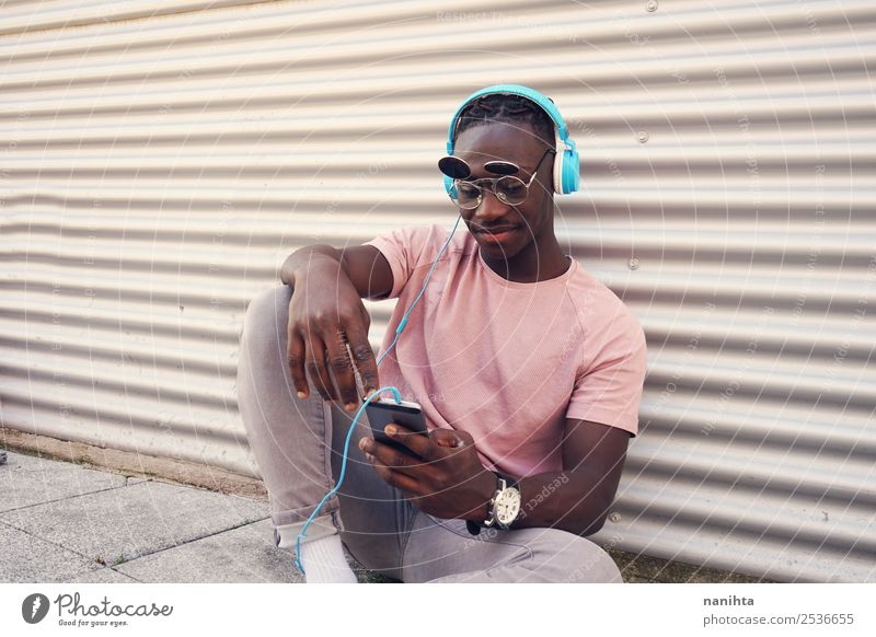 Young man listening to music and use his smartphone Lifestyle Style Design Joy Leisure and hobbies Freedom Cellphone Headset PDA Headphones Technology