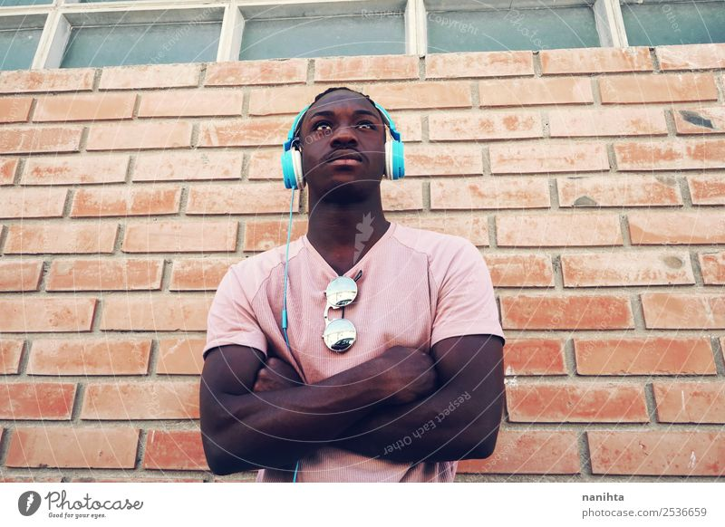 Young strong man listening to music Human being Youth (Young adults) Man Town Young man 18 - 30 years Black Lifestyle Adults Style Orange Leisure and hobbies