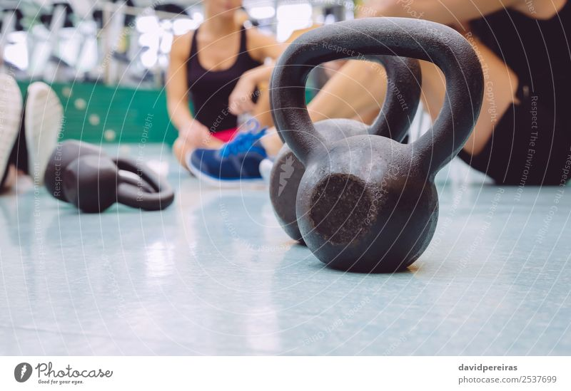Black iron kettlebell on the floor of fitness center Woman Man Lifestyle Adults Sports Group Together Friendship Body Power Action Authentic Fitness Strong