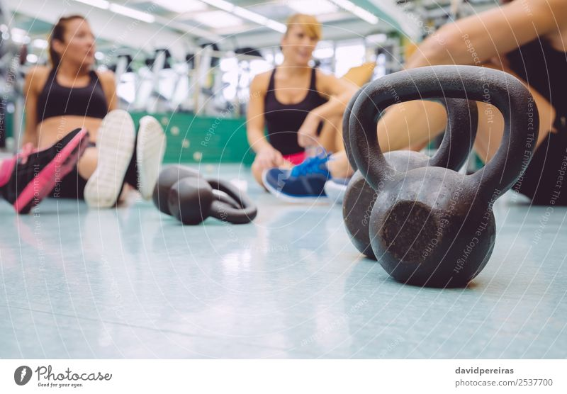 Black iron kettlebell on the floor of fitness center Lifestyle Body Club Disco Sports Woman Adults Man Friendship Group Fitness Authentic Together Muscular