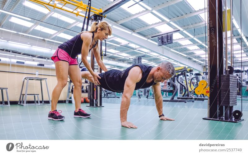 Personal trainer teaching to man in suspension training Lifestyle Beautiful Body Sports Work and employment Woman Adults Man Fitness Authentic Muscular Strong