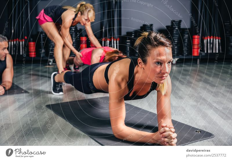 Woman doing push ups with trainer in background Happy Body Sports School Adults Man Arm Group Fitness Authentic Muscular Strong pushup Core Practice Gymnasium