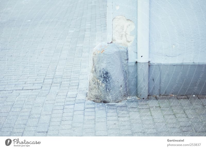 corner Downtown Deserted Wall (barrier) Wall (building) Bright Blue Corner Rain gutter Bollard Cobblestones Street life Colour photo Subdued colour
