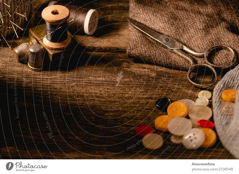 Close-up of wooden sewing spool and buttons set on wooden table Leisure and hobbies Table Workplace Craft (trade) Tool Scissors Accessory Wood Metal Bright