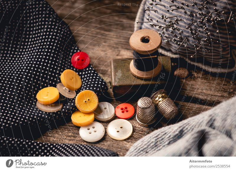 Close-up of wooden sewing spool and buttons set on wooden table Leisure and hobbies Table Workplace Craft (trade) Tool Cloth Accessory Wood Metal Black