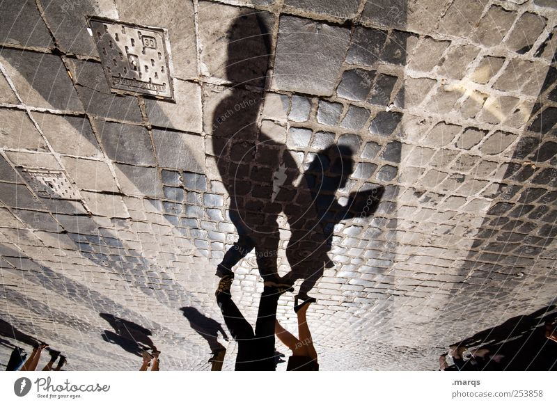 tell me what Human being Child Parents Adults Pedestrian Sign Stripe Going Cobblestones Zebra crossing Colour photo Abstract Structures and shapes Shadow