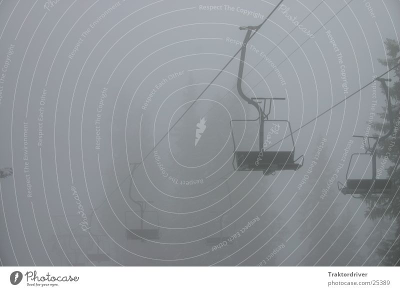 Chairlift in the fog Chair lift Ski lift Fog Empty Gloomy Fir tree Armchair Black Gray Grief Sports Loneliness Rope Sadness Cloud cover