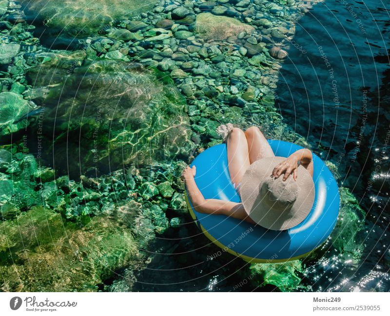Woman with pamela on a float on a mountain river Human being Feminine Adults Life Body 1 45 - 60 years Nature Water Sun Summer Warmth Rock Mountain River bank