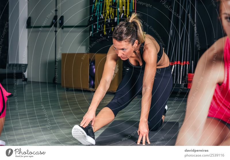 Woman stretching legs in a fitness class Lifestyle Happy Beautiful Body Leisure and hobbies Sports School Human being Adults Arm Group Braids Fitness Authentic