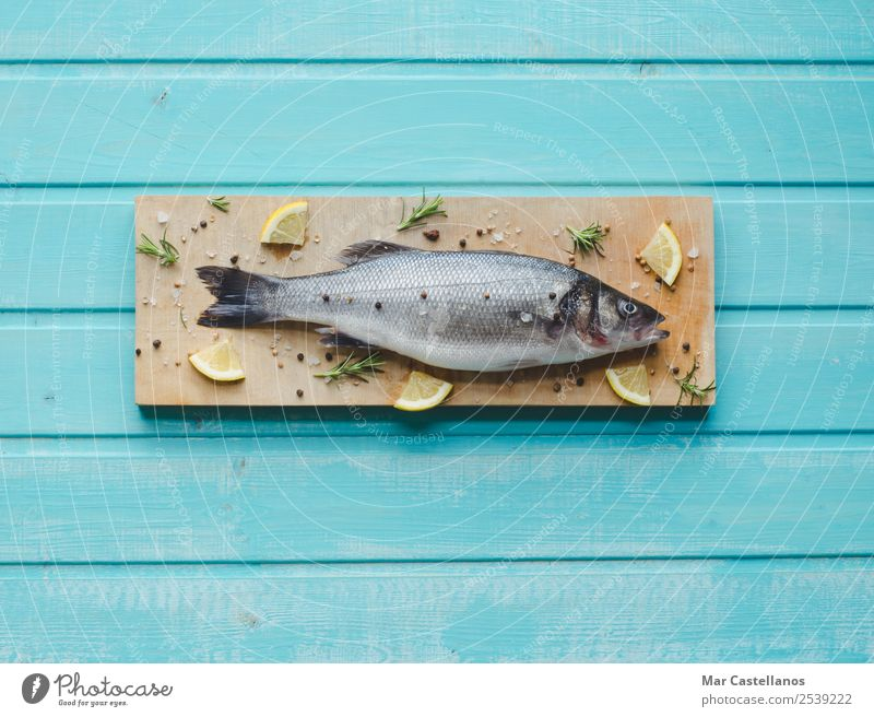 Sea bass on kitchen table with lemon and rosemary Seafood Herbs and spices Eating Dinner Diet Table Restaurant Animal Wood Write Fresh Delicious Blue