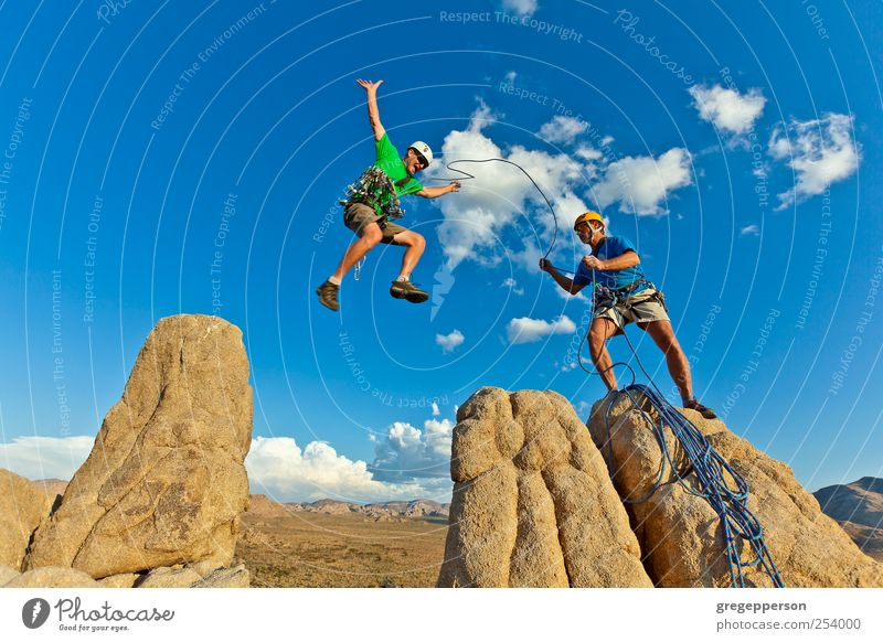 Climbing team charging for the summit. Human being Man Adults Life Sports Jump Masculine Adventure Rope Success Team Trust Peak Risk Brave