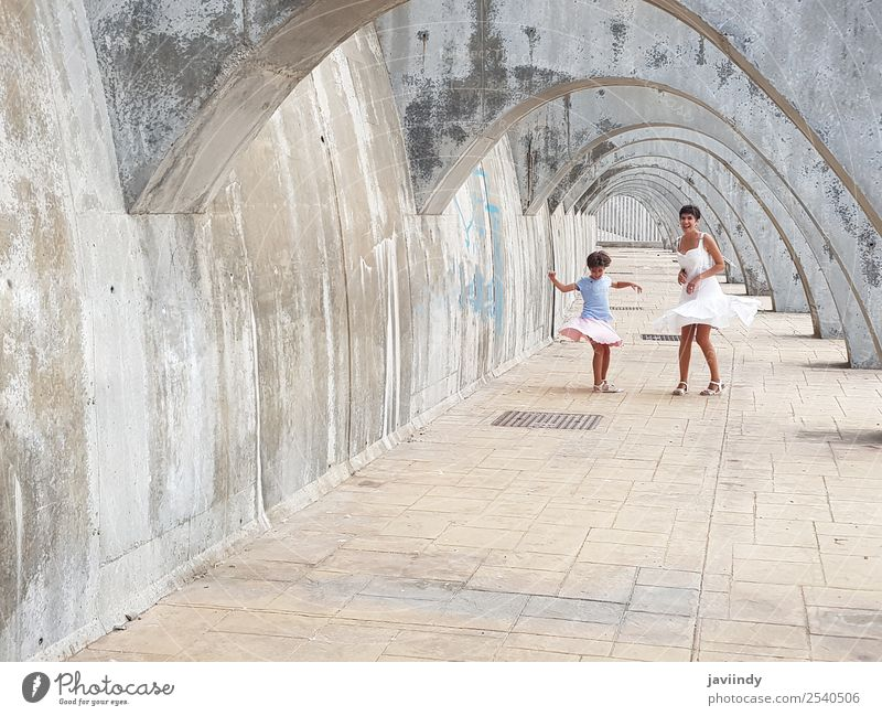 Funny mother and daughter dancing under arches Lifestyle Style Joy Happy Beautiful Playing Summer Dance Child Human being Feminine Woman Adults Parents Mother