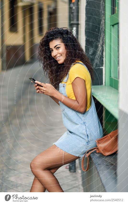 African woman texting with her smart phone. Lifestyle Style Happy Beautiful Hair and hairstyles Telephone PDA Technology Human being Feminine Girl Young woman