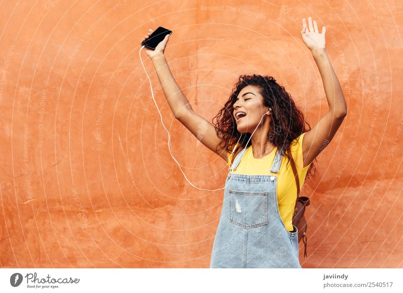 Happy Arab girl listening to music and dancing Lifestyle Style Beautiful Hair and hairstyles Music Telephone PDA Technology Human being Feminine Young woman