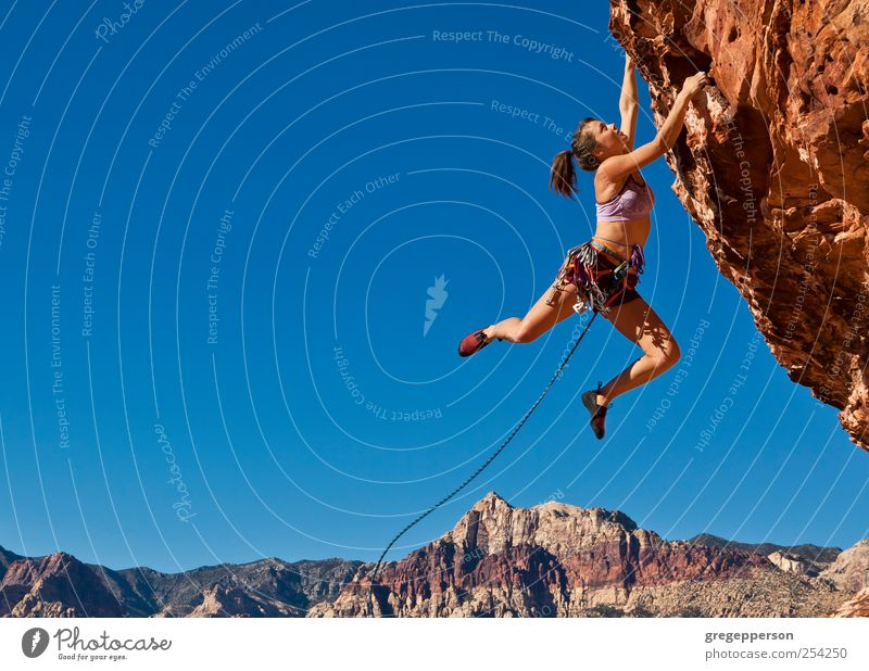 Rock climber on the edge. Human being Youth (Young adults) Loneliness Adults Life Sports Power Adventure Rope Success 18 - 30 years Young woman Climbing Trust Risk Brave