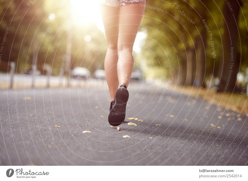 Young woman jogging down an autumn street Lifestyle Relaxation Summer Sun Sports Jogging Human being Woman Adults Feet Street Footwear Fitness Behind running