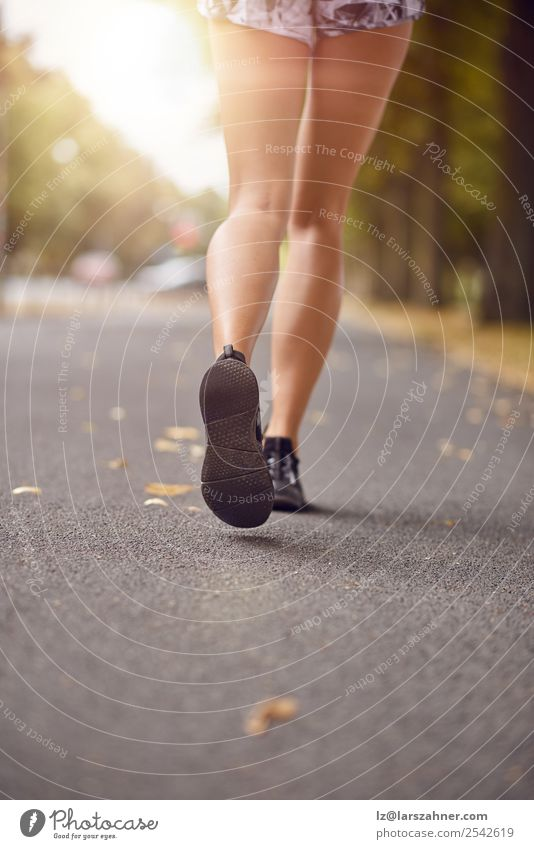 Young woman jogging down an autumn street Lifestyle Relaxation Summer Sun Sports Jogging Human being Woman Adults Feet 1 18 - 30 years Youth (Young adults)