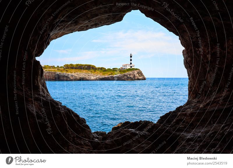 Portocolom Lighthouse on a cliff seen from a cave. Vacation & Travel Tourism Trip Sightseeing Cruise Summer Summer vacation Ocean Island Nature Landscape Coast