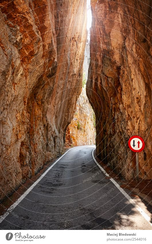 Narrow road cut through a mountain. Vacation & Travel Trip Adventure Expedition Camping Cycling tour Sun Mountain Nature Rock Canyon Road sign Willpower Brave