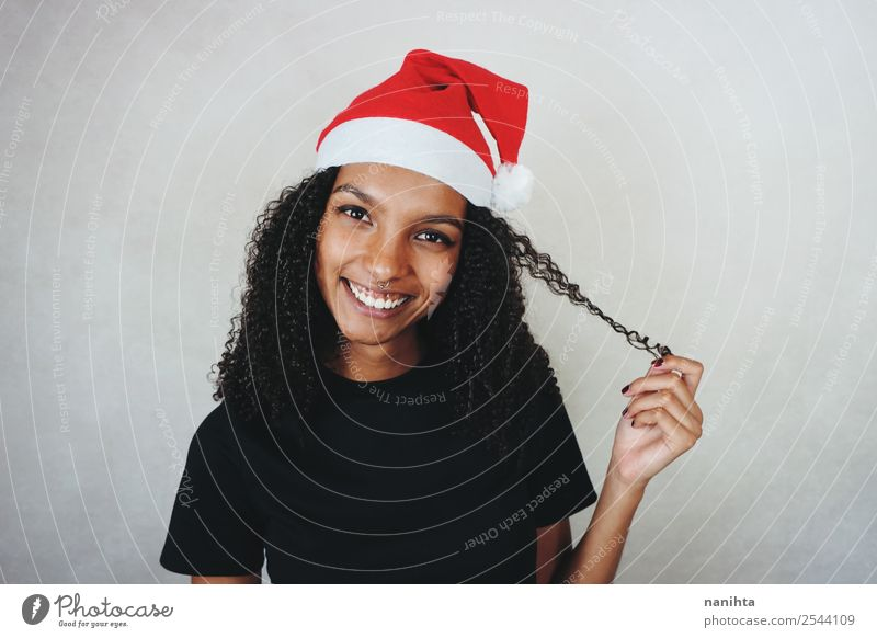 Young happy woman wearing a santa hat Lifestyle Style Design Joy Beautiful Hair and hairstyles Feasts & Celebrations Christmas & Advent New Year's Eve