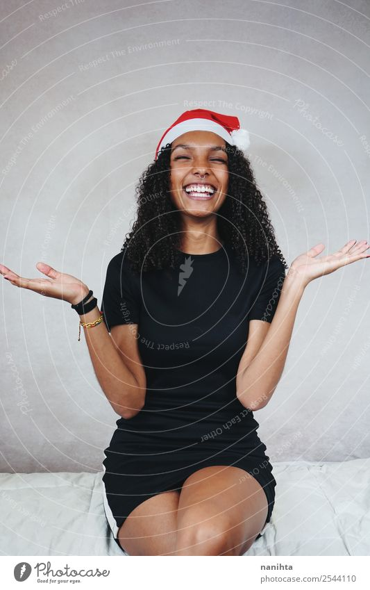 Happy young woman wearing a santa claus hat Woman Human being Youth (Young adults) Young woman Christmas & Advent Beautiful Joy 18 - 30 years Black Lifestyle