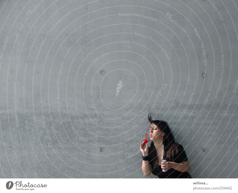 Woman blowing soap bubbles with abandon in front of grey wall, neutral background Adults 1 Human being Wall (barrier) Wall (building) Brunette Playing Gray Ease