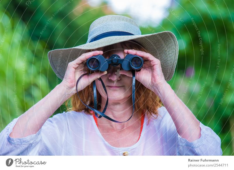 "a woman with a hat looks through binoculars Human being Feminine Woman Adults 1 Hat Observe Looking Friendliness Curiosity ""Woman Binoculars,"" Colour photo"