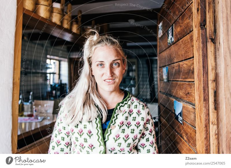 Young woman in alpine hut Style Feminine Youth (Young adults) 18 - 30 years Adults Hut Costume Cardigan Blonde Long-haired Work and employment Smiling Laughter