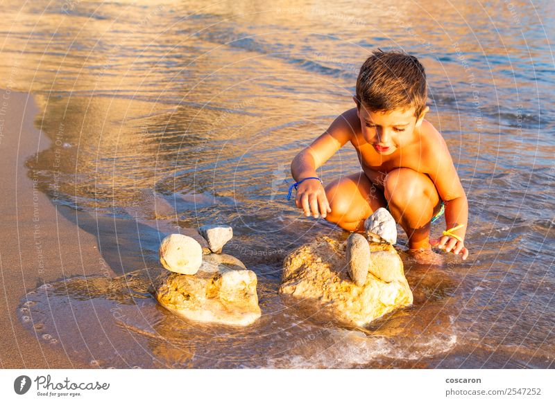 Little kid making constructions with stones on the beach Child Human being Vacation & Travel Summer Blue Sun Ocean Relaxation Joy Beach Lifestyle Coast Happy