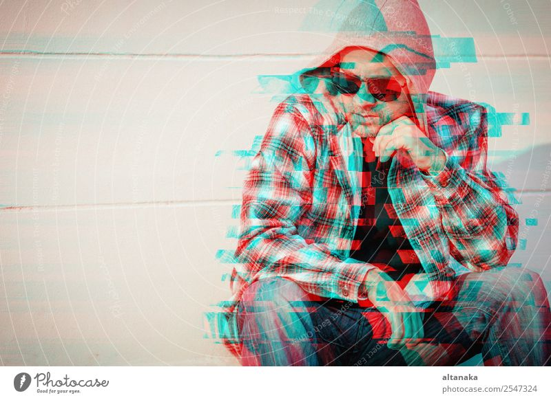 Portrait of a one sad man in sunglasses sitting outdoors near the house at the day time. Concept of sadness. Glitched style photo. Lifestyle Face Human being