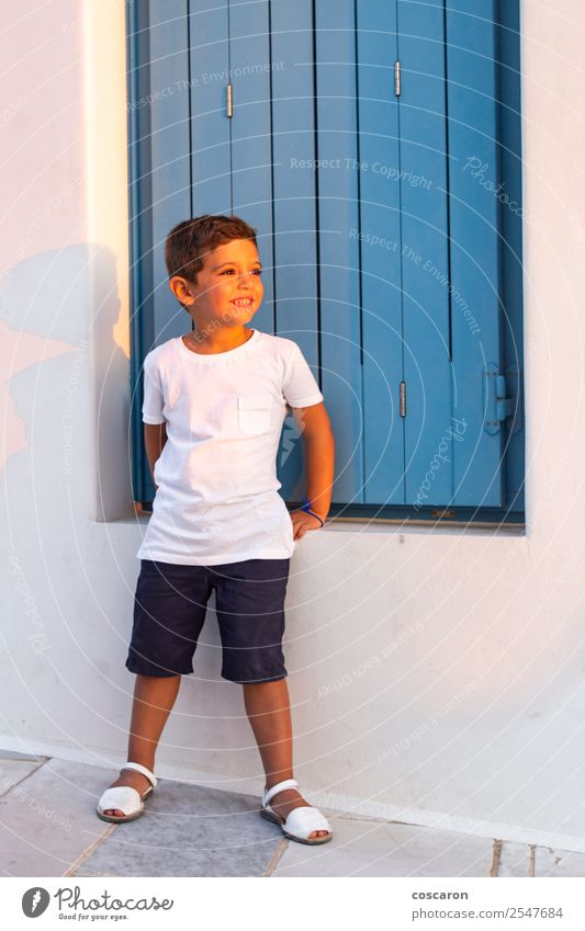 Cute child near of a wooden blue window at sunset Lifestyle Design Happy Beautiful Vacation & Travel Summer Island House (Residential Structure) Child
