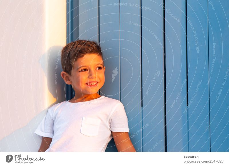 Cute child near of a wooden blue window at sunset Child Human being Summer Blue Beautiful White House (Residential Structure) Joy Window Face Lifestyle Wood