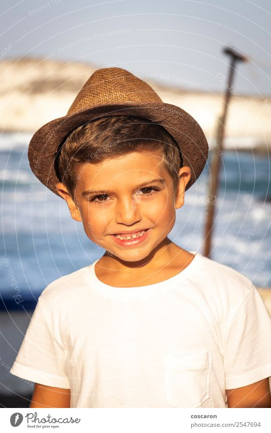 Portrait of a cute kid with hat in front of a ocean Lifestyle Joy Happy Beautiful Face Leisure and hobbies Vacation & Travel Summer Sun Beach Ocean Child