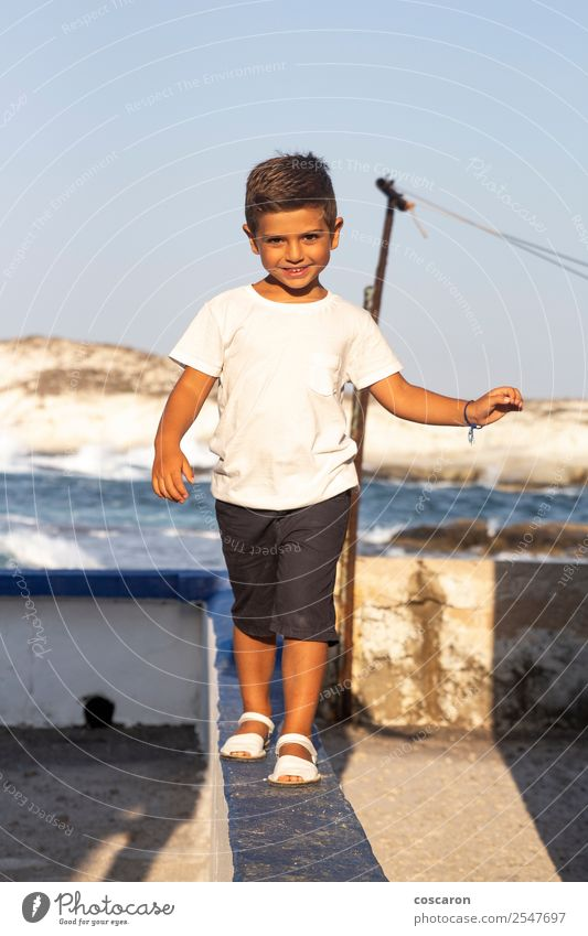 Cute boy doing balance on a wall in summer Child Human being Nature Summer Blue Beautiful White Joy Boy (child) Small Playing Fashion Stone Rock