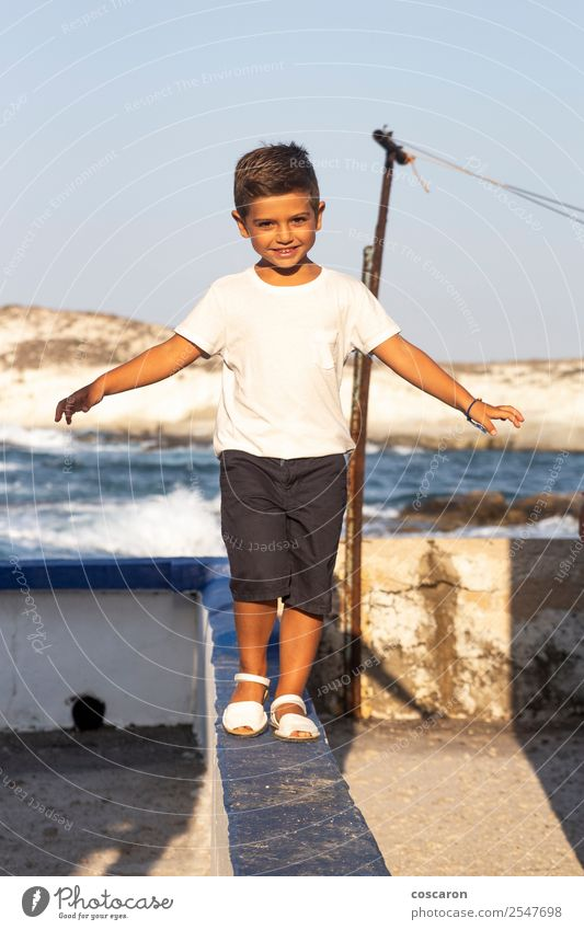 Cute boy doing balance on a wall in summer Child Human being Nature Summer Beautiful Sun White Ocean Joy Lifestyle Coast Boy (child) Small Playing Fashion Stone