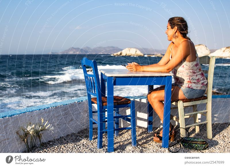 Middle aged woman seated in a table of a restaurant near the sea Woman Human being Nature Vacation & Travel Man Summer Beautiful Water Hand Ocean Relaxation