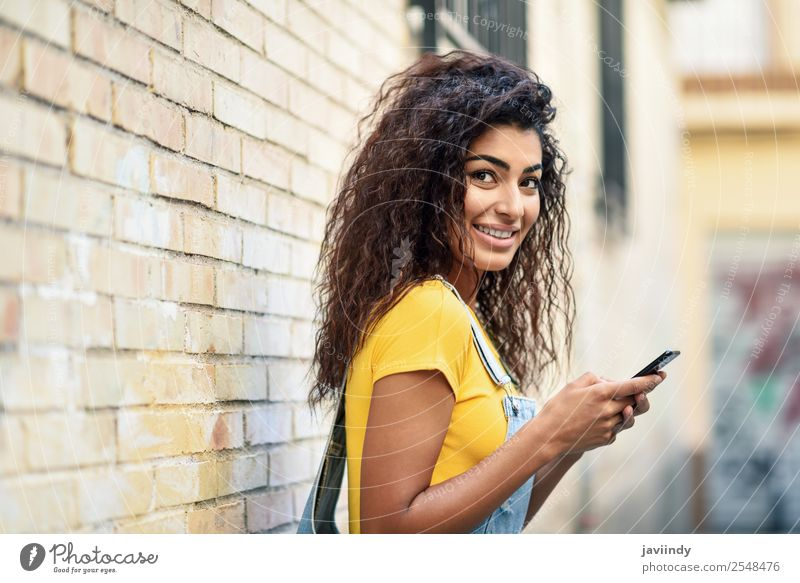 Young Arab woman texting with her smart phone Lifestyle Style Happy Beautiful Hair and hairstyles Telephone PDA Technology Human being Feminine Girl Young woman